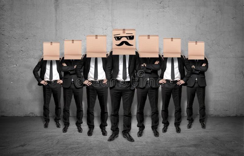 Руководитель и его штат оставаясь вместе с коробками на их головах стоковая фотография rf