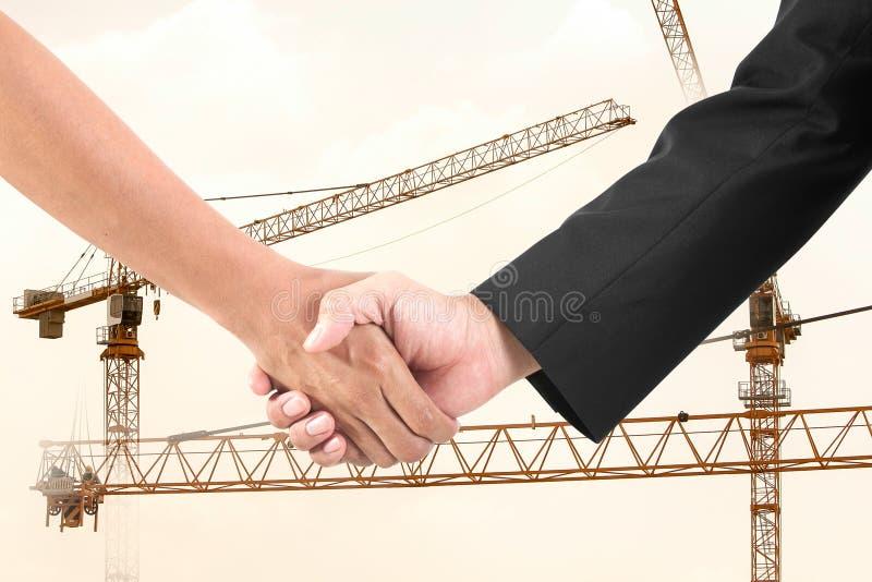Рукопожатие бизнесмена в кране конструкции. стоковые фотографии rf