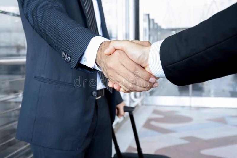 Рукопожатие бизнесменов на авиапорте - концепция деловых поездок стоковые фото