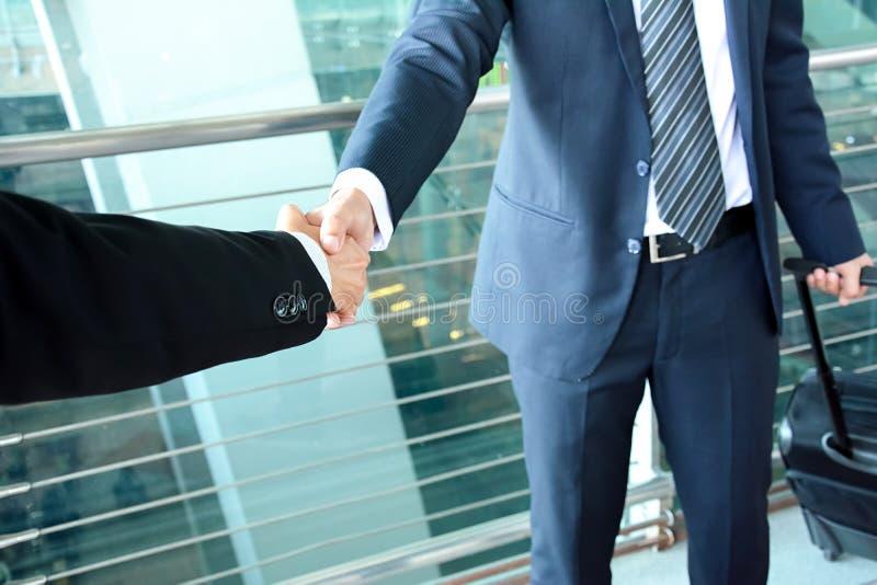 Рукопожатие бизнесменов на авиапорте - концепция деловых поездок стоковое фото rf