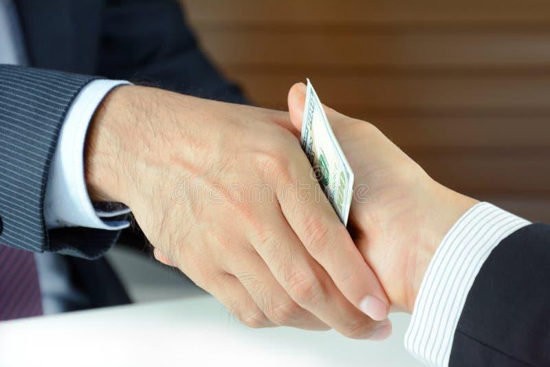 Рукопожатие бизнесменов с деньгами стоковое изображение