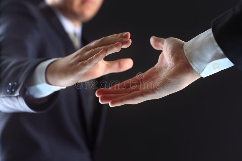 Рукопожатие в черной предпосылке стоковая фотография rf