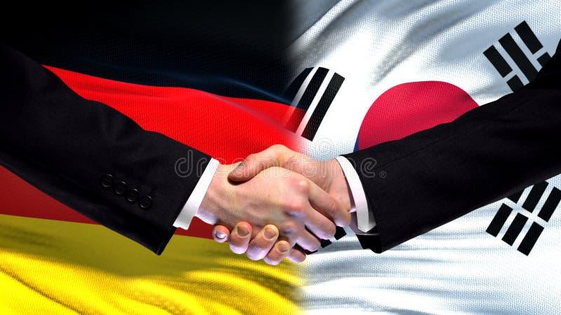 Рукопожатие Германии и Южной Кореи, международное приятельство, предпосылка флага стоковые фотографии rf