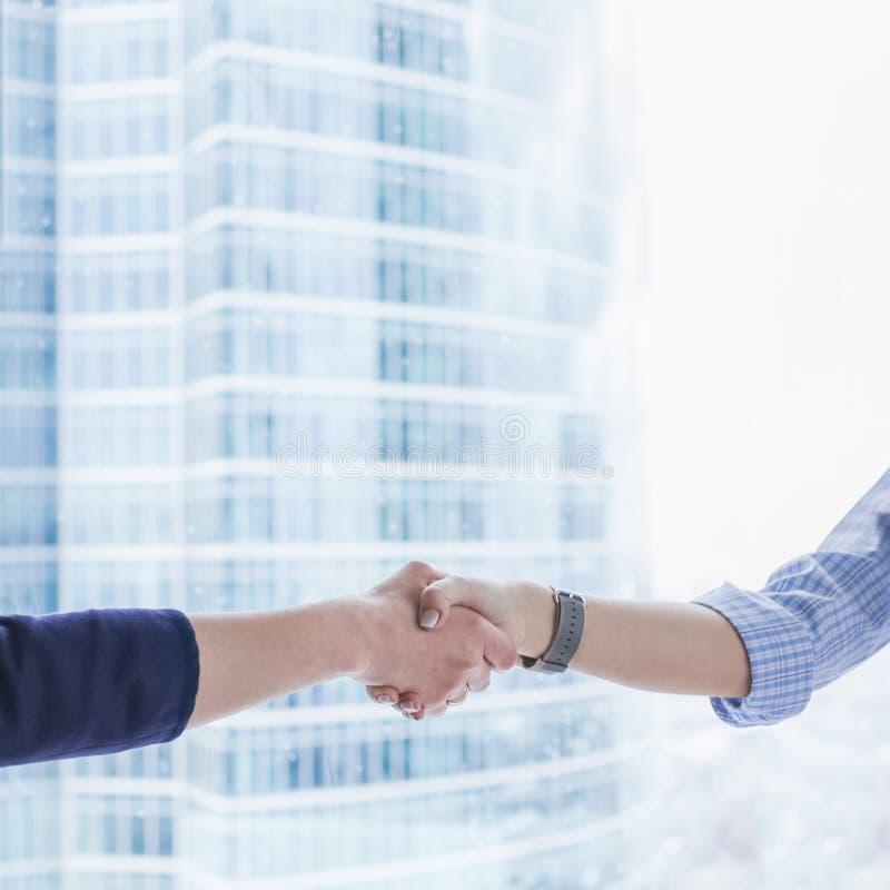 Рукопожатие дела женщин Рукопожатие 2 бизнес-леди над предпосылкой офисных зданий стоковые фото