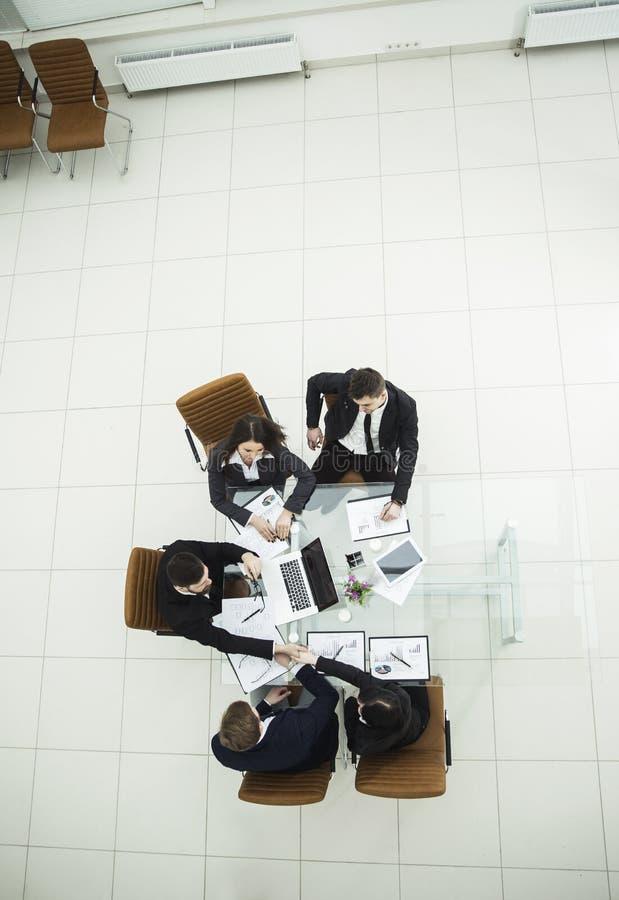 Рукопожатие деловых партнеров на деловой встрече на рабочем месте стоковые фото