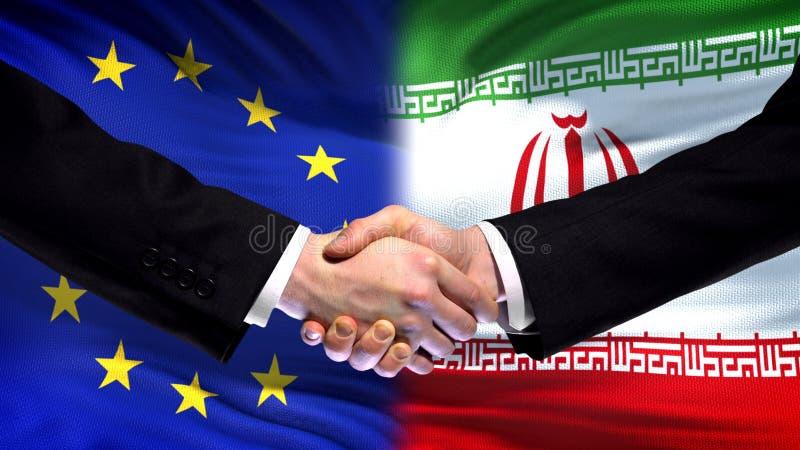 Рукопожатие Европейского союза и Ирана, международное приятельство, предпосылка флага стоковая фотография rf