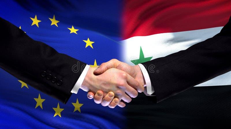 Рукопожатие Европейского союза и Сирии, международное приятельство, предпосылка флага стоковая фотография rf