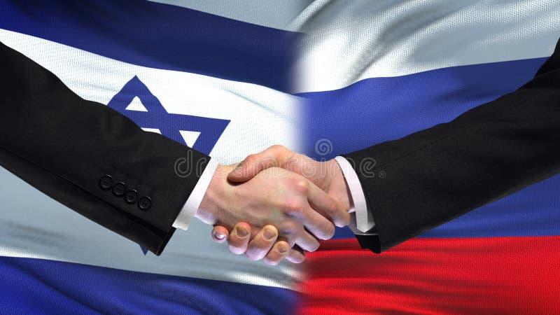 Рукопожатие Израиля и России, международные отношения приятельства, предпосылка флага стоковая фотография rf
