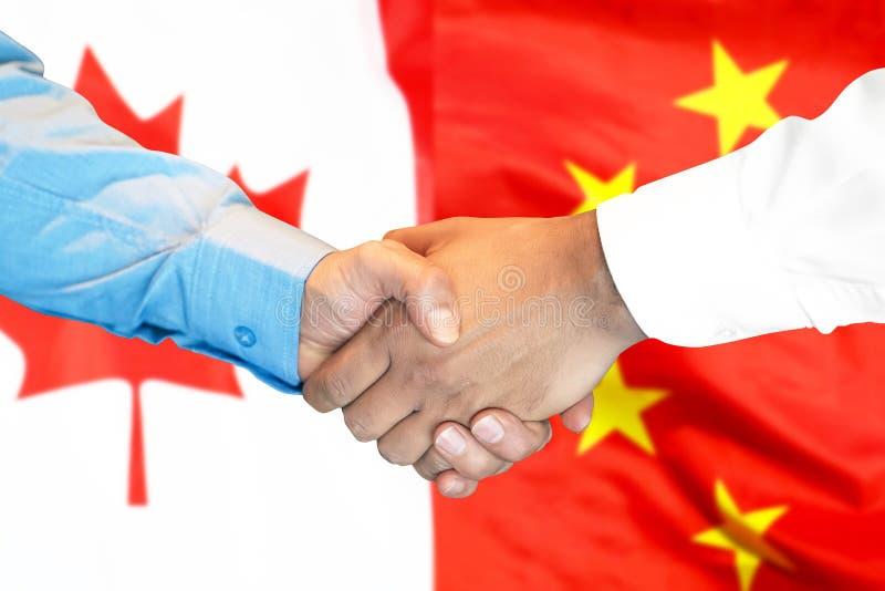 Рукопожатие на предпосылка флаге Канады и Китая стоковое изображение