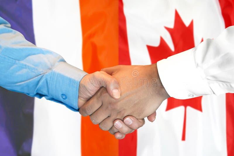 Рукопожатие на предпосылка флаге Франции и Канады стоковые фото