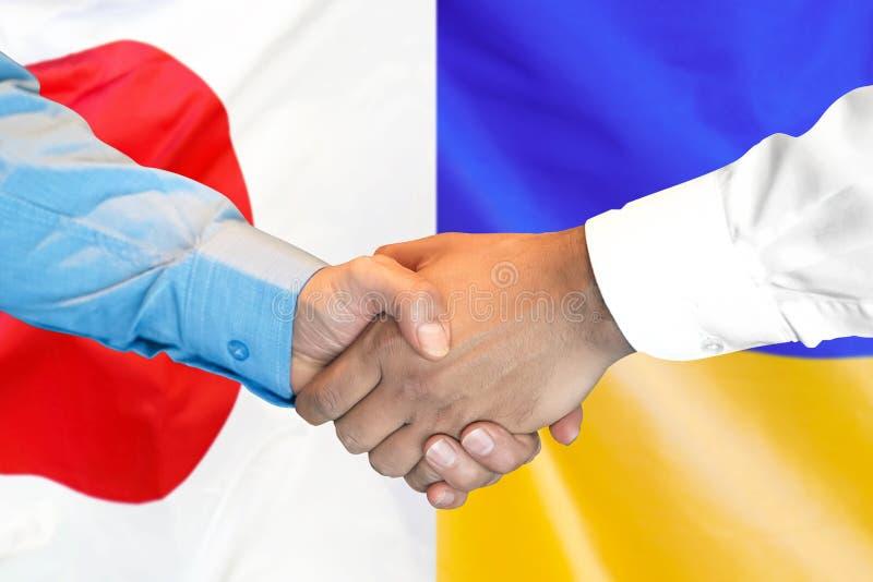Рукопожатие на предпосылка флаге Японии и Украины стоковое изображение