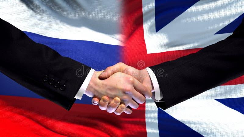 Рукопожатие России и Великобритании, международное приятельство, предпосылка флага стоковые фотографии rf