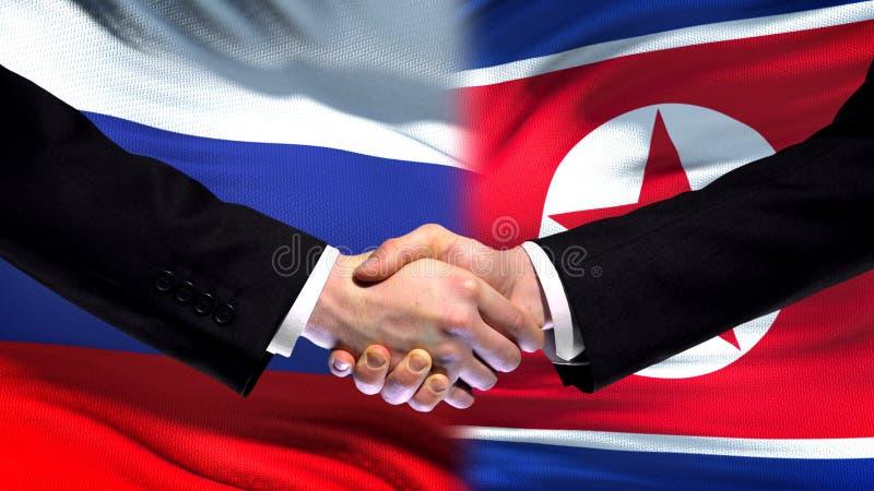 Рукопожатие России и Северной Кореи, международное приятельство, предпосылка флага стоковая фотография rf