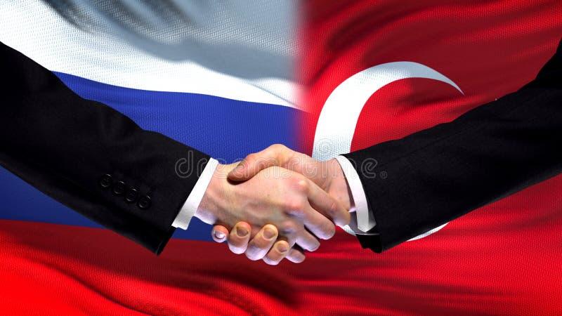 Рукопожатие России и Турции, международные отношения приятельства, предпосылка флага стоковая фотография rf