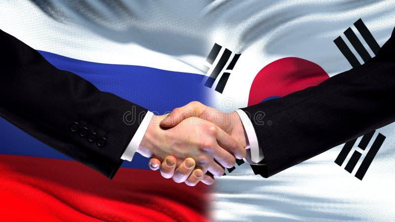 Рукопожатие России и Южной Кореи, международное приятельство, предпосылка флага стоковые фотографии rf