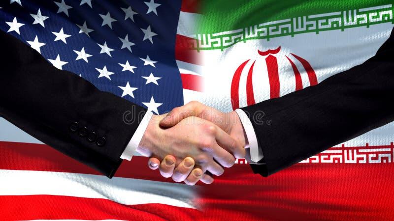Рукопожатие Соединенных Штатов и Ирана, международное приятельство, предпосылка флага стоковая фотография rf