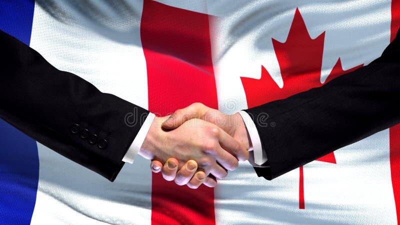 Рукопожатие Франции и Канады, международные отношения приятельства, предпосылка флага стоковая фотография rf