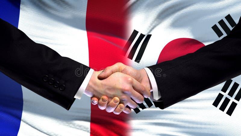 Рукопожатие Франции и Южной Кореи, международное приятельство, предпосылка флага стоковые фото