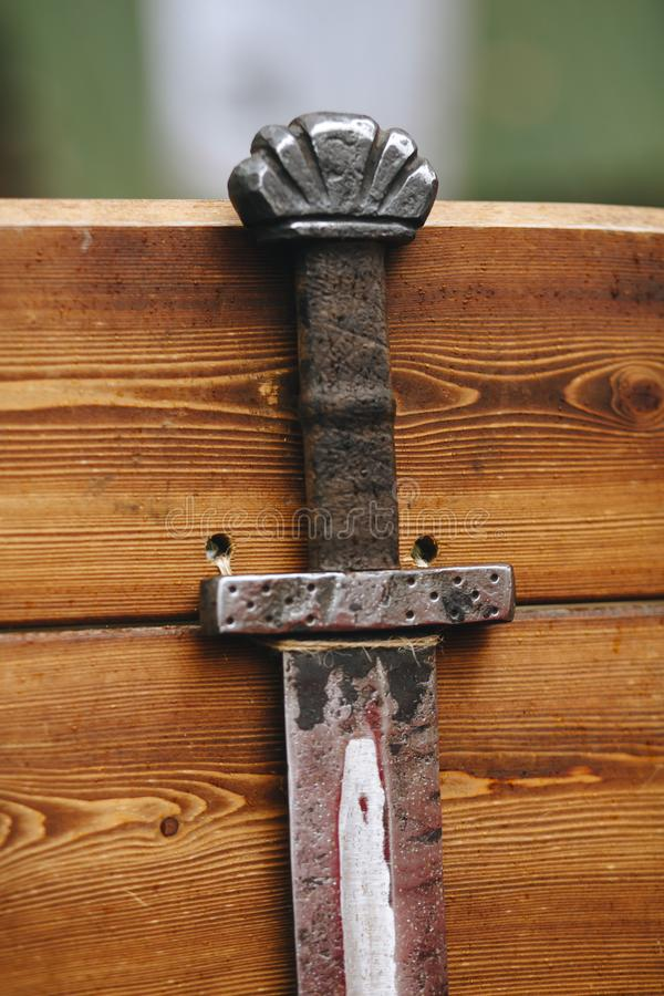 Рукоятка и часть лезвия шпаги, половина нажали из оболочки, конца-вверх против запачканной деревянной стены стоковое изображение rf
