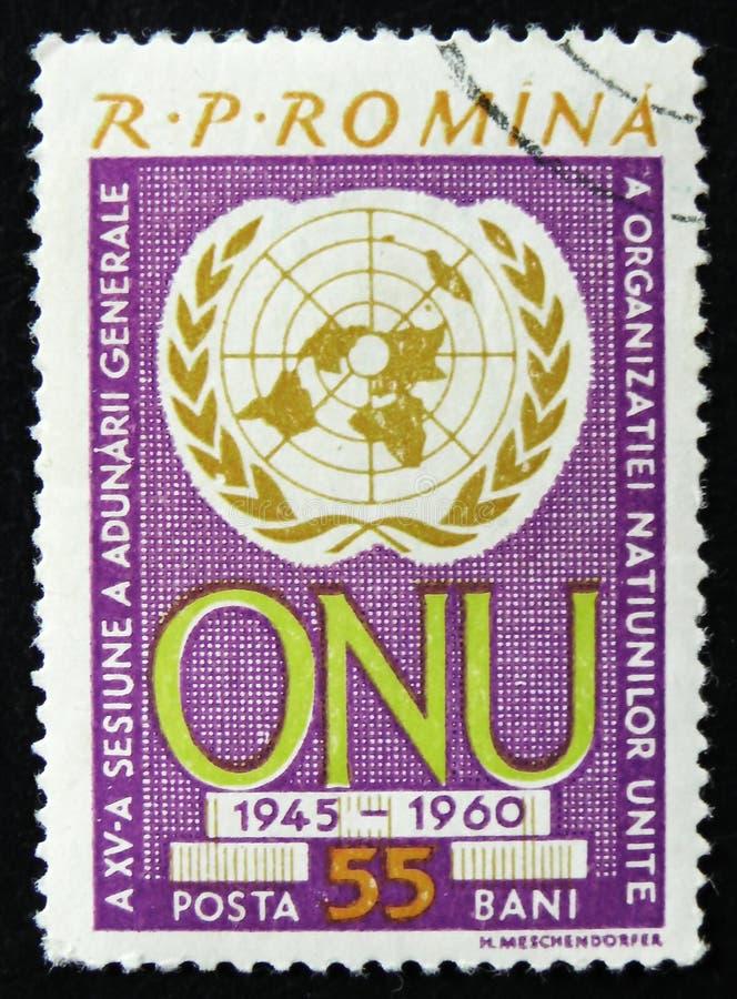 Румынский штемпель показывает эмблему организации ОбъединЕнной нации, годовщину 15, около 1960 стоковые фото