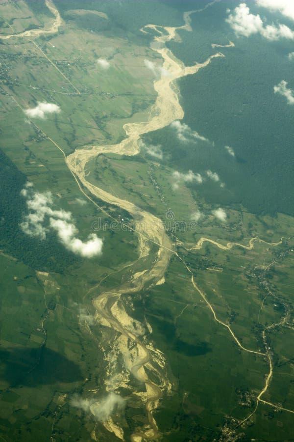 Русло реки с песочными банками в зеленой долине полей и лесов от большей высоты облака воздушного фотографирования белые над стоковое фото