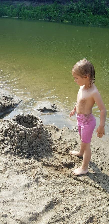 Русская девушка реки в розовом заплывании замыкает накоротко замок песка стоковые фотографии rf
