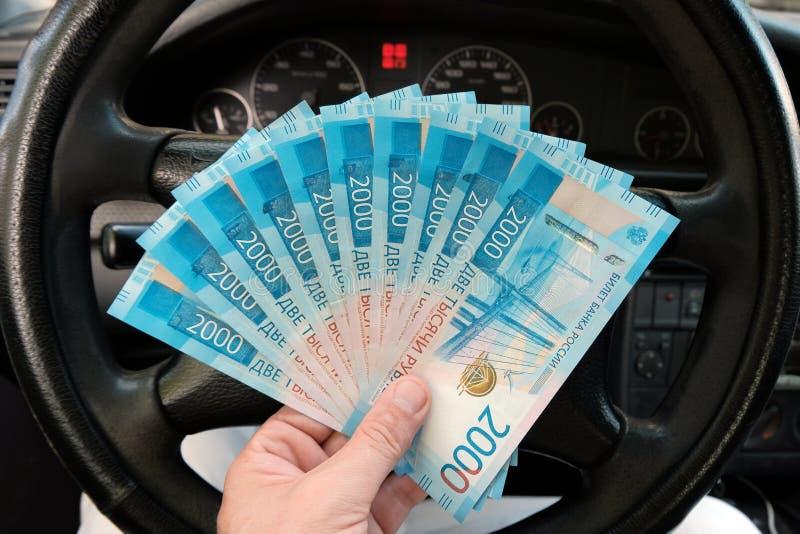 Русские деньги в мужской руке на предпосылке руля в автомобиле 20 тысяч рубли Концепция заработков стоковые фото