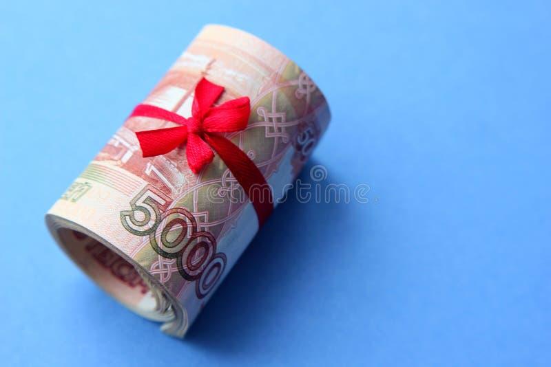 Русские деньги 5000 рублей переплетенных в трубку и связанных с лентой, на покрашенной предпосылке стоковая фотография