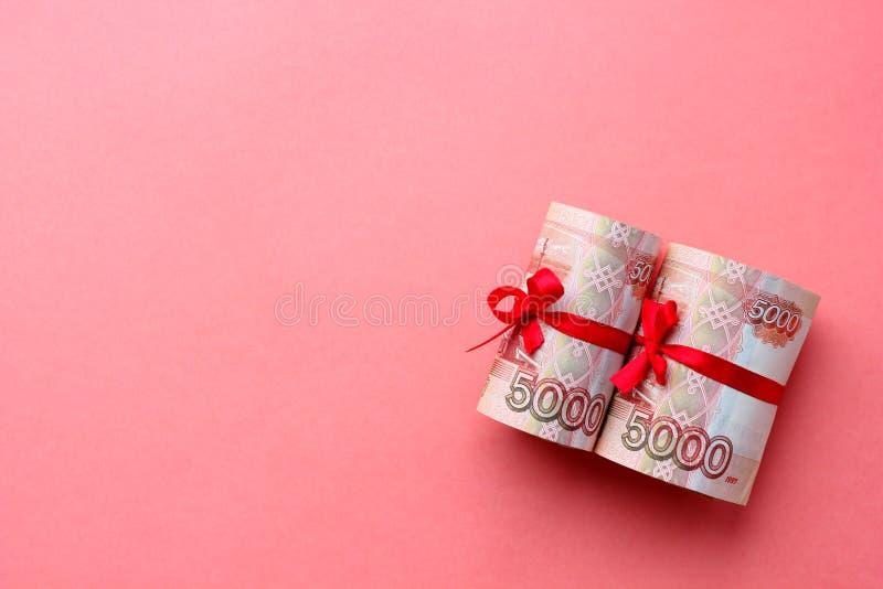 Русские деньги 5000 рублей переплетенных в трубку и связанных с лентой, на покрашенной предпосылке стоковые фотографии rf