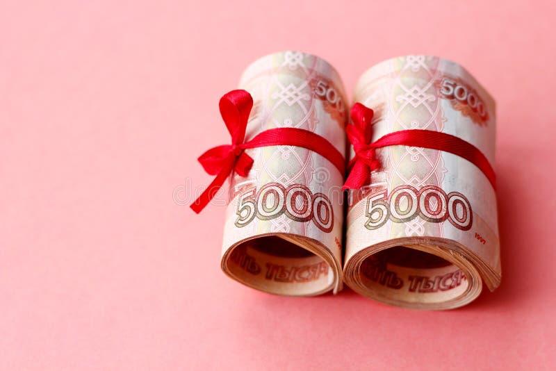Русские деньги 5000 рублей переплетенных в трубку и связанных с лентой, на покрашенной предпосылке стоковое фото