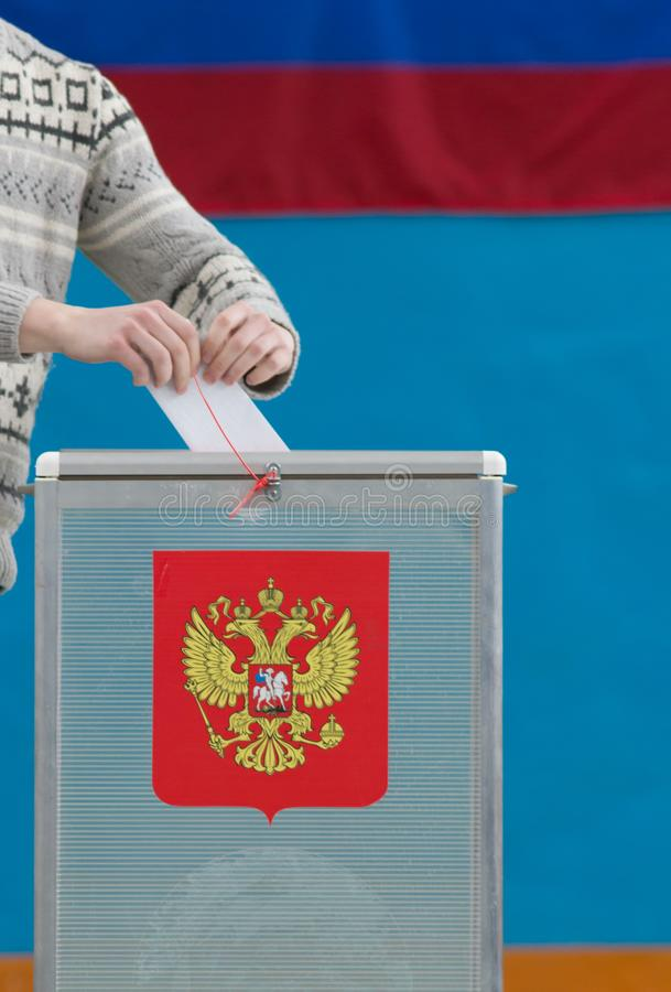Русские президентские выборы - человек кладет избирательный бюллетень к голосуя коробке стоковое фото rf
