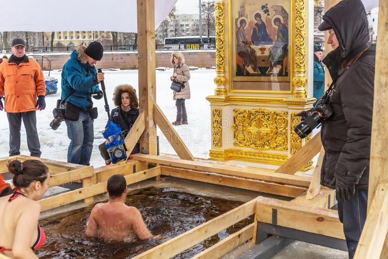 Русские люди окунуты в отверстие льда в день явления божества на стенах крепости Питера и Пола стоковые изображения rf
