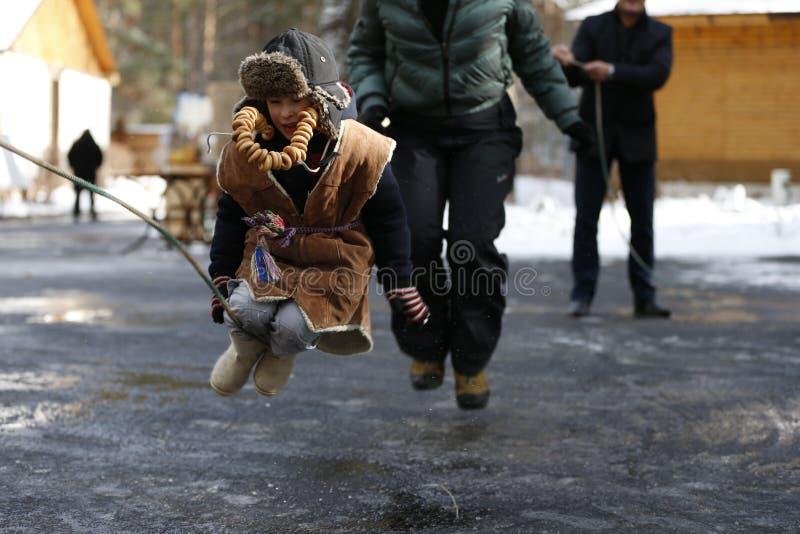 Русский национальный праздник Maslyanitsa Мальчик скачет над веревочкой стоковые изображения rf