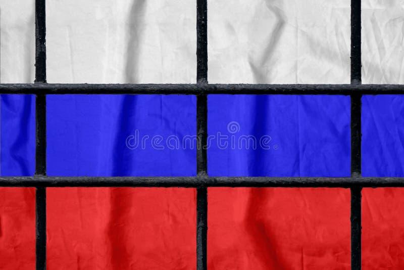 Русский флаг за черными барами тюрьмы металла стоковое изображение