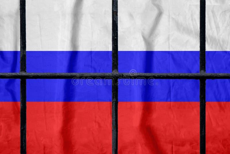 Русский флаг за черными барами тюрьмы металла стоковая фотография