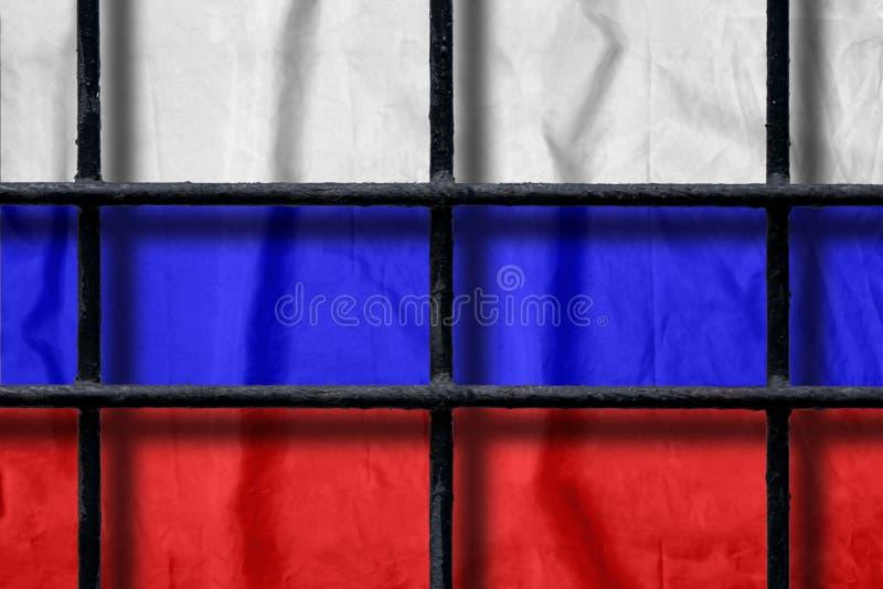 Русский флаг за черными барами тюрьмы металла с тенями стоковые изображения