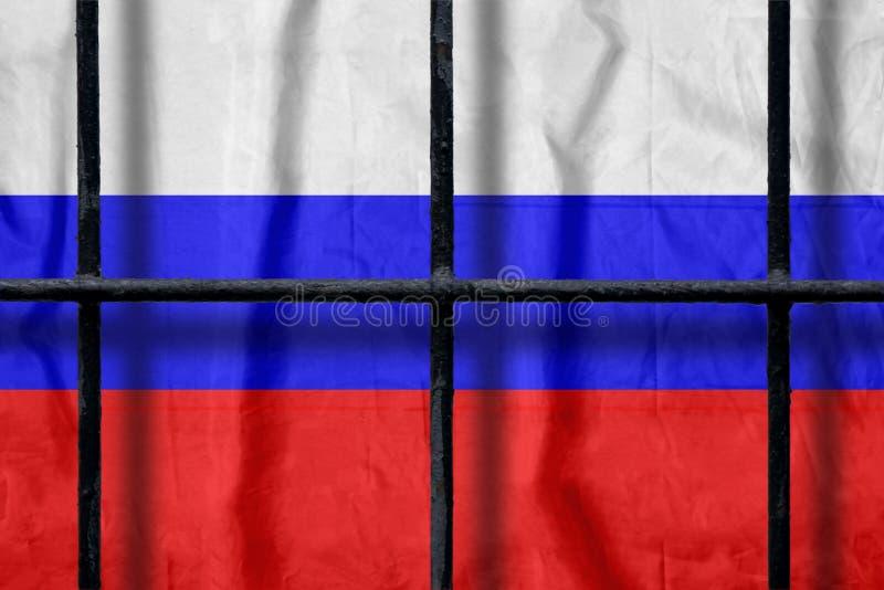 Русский флаг за черными барами тюрьмы металла с тенями стоковое фото