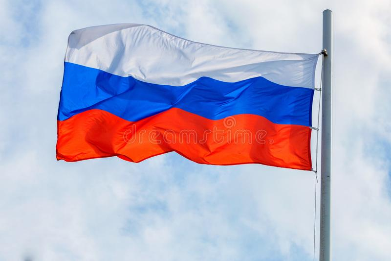 Русский флаг на предпосылке неба и облака стоковое изображение rf