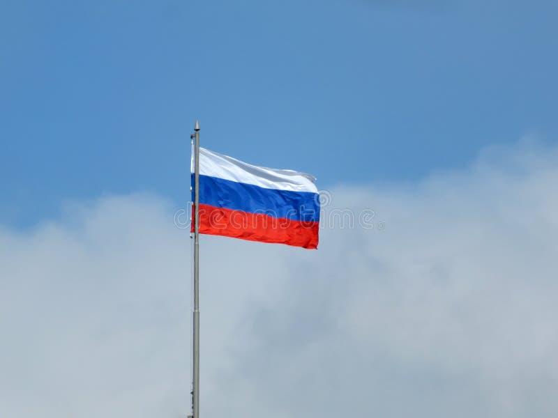 Русский флаг на предпосылке пасмурного голубого неба стоковая фотография