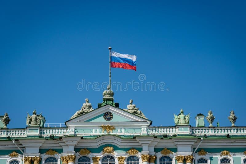 Русский флаг развевая на верхней части музея обители в Санкт-Петербурге стоковое фото rf