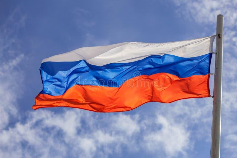 Русский флаг на предпосылке неба и облака стоковая фотография