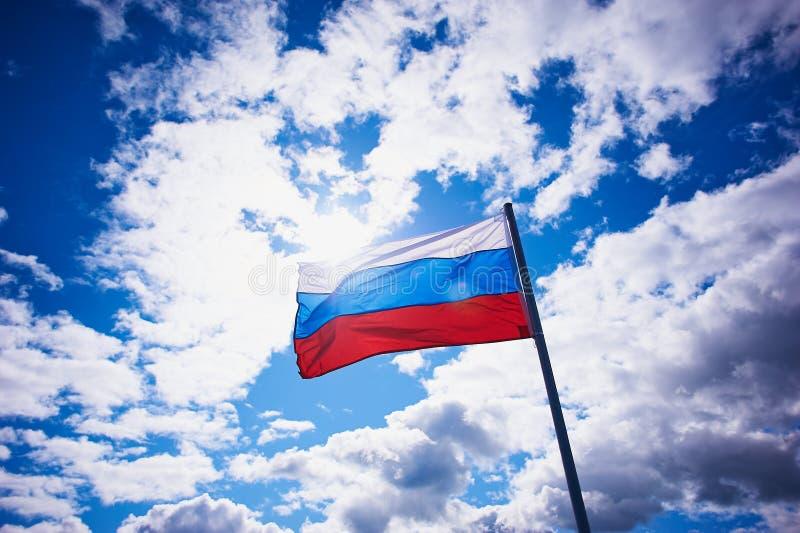 Русский флаг на предпосылке яркого неба с объемными облаками патриотическо стоковое изображение rf
