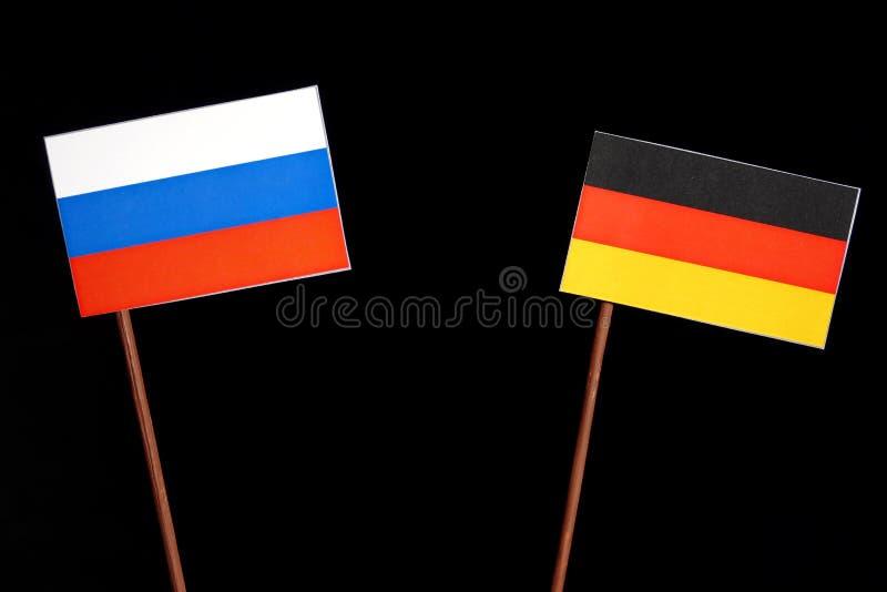 Русский флаг с немецким флагом на черноте стоковые фотографии rf