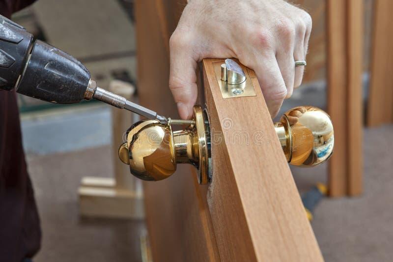 Ручка двери установки с замком, woodworkerÂ привинтила винт, usi стоковое изображение rf