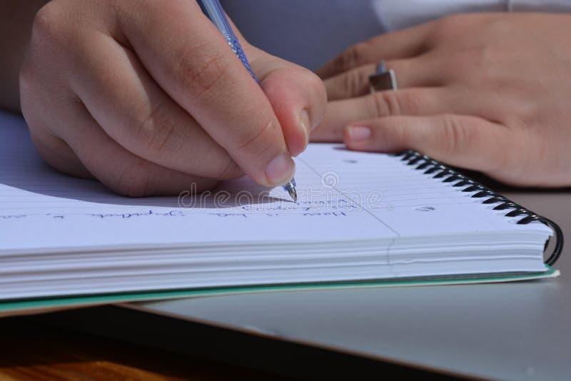 Ручка в руке, сочинительстве женщины в скрепленной спиралью тетради стоковое изображение