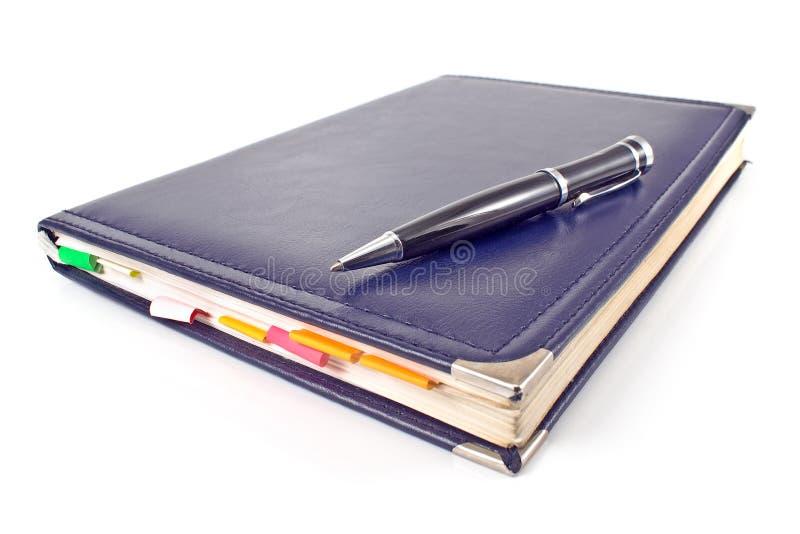 Ручка и голубая тетрадь стоковая фотография rf