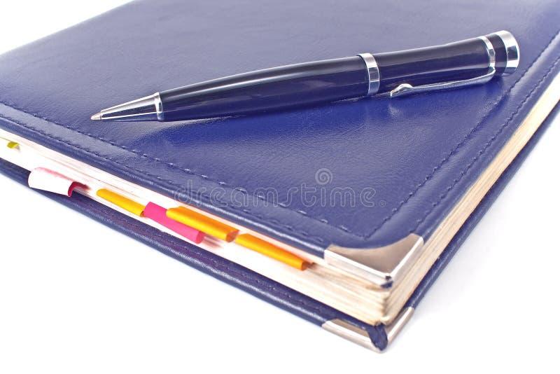 Ручка и голубая тетрадь стоковое изображение rf