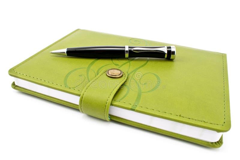 Ручка и зеленая тетрадь стоковые изображения rf