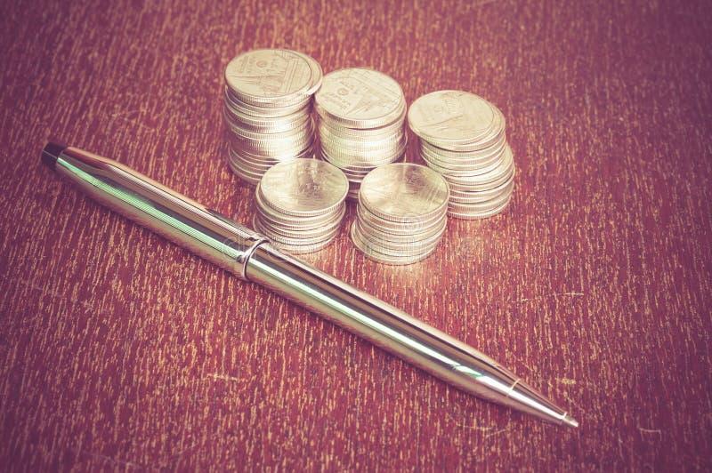 Ручка и монетки стоковая фотография