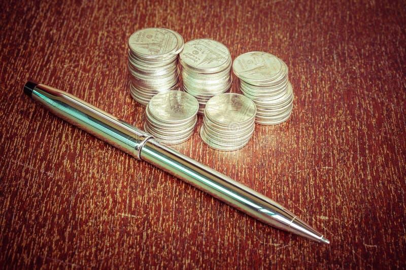 Ручка и монетки стоковое фото
